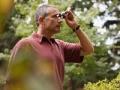 Hombre observando aves con unos binoculares. McAllen, TX, es un punto de acceso para los observadores de aves, con más de 500 especies de aves documentadas.
