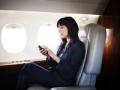 Mujer con un teléfono inteligente en un avión, aplicaciones de viaje favoritas de Samantha Brown