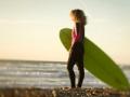 Mujer con tabla de surfear en La Jolla, California, 7 escapadas para las mujeres