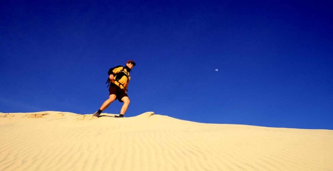 Man hiking on Kelso Dunes, Mojave National Preserve, California