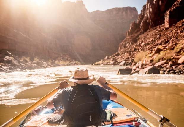 Un hombre rema un bote en el Río Colorado, en el Gran Cañon - Experiencias increíbles en los parques nacionales