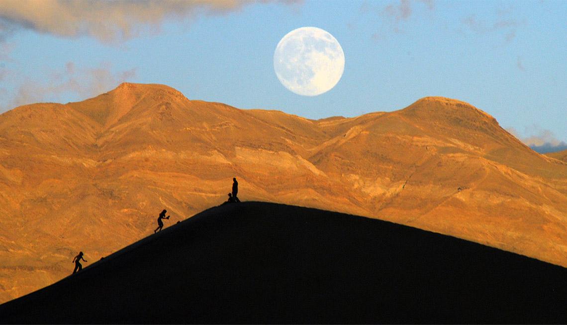 item 6 of Gallery image - Una luna llena se levanta sobre las personas que suben a una duna de arena.