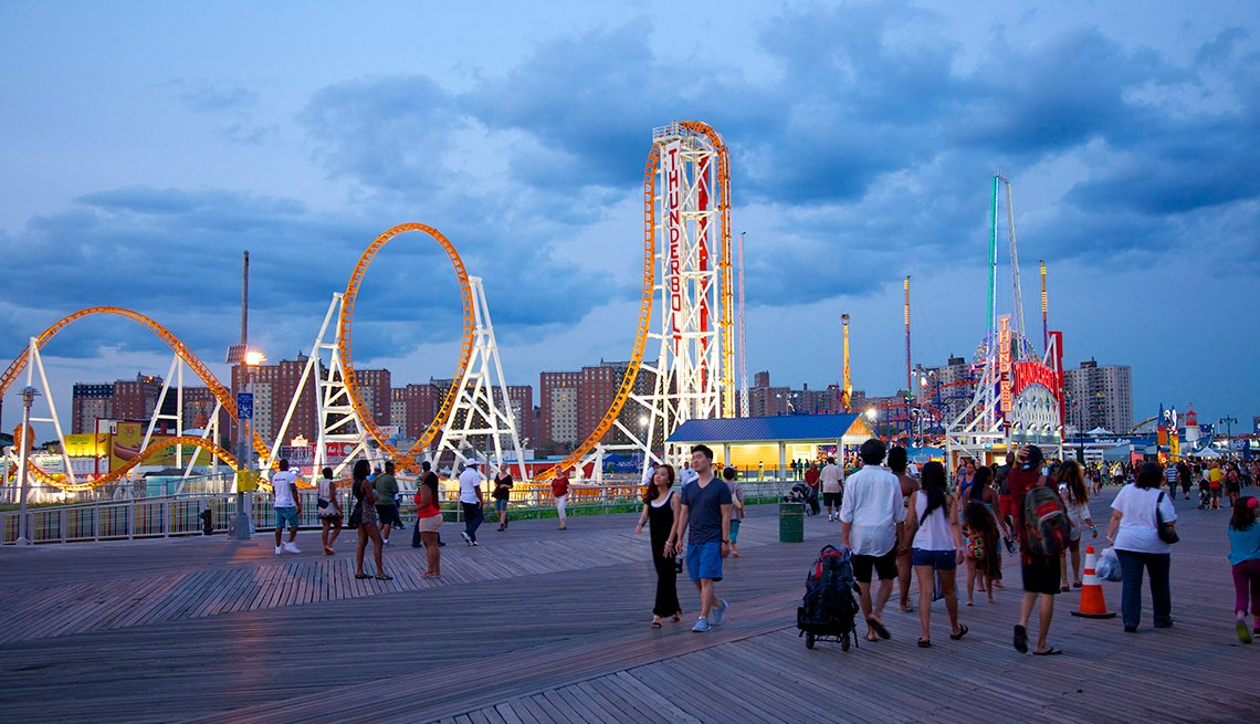 people walking along Coney Island boardwalk at dusk
