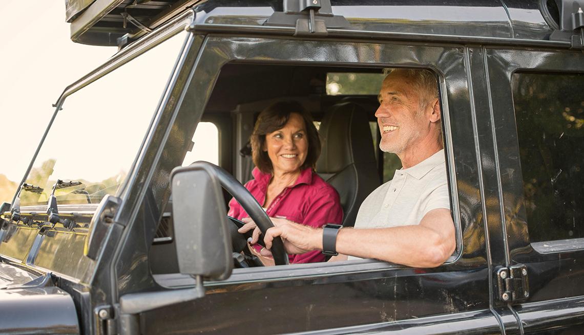 Un hombre maneja un vehículo acompañado de una mujer.
