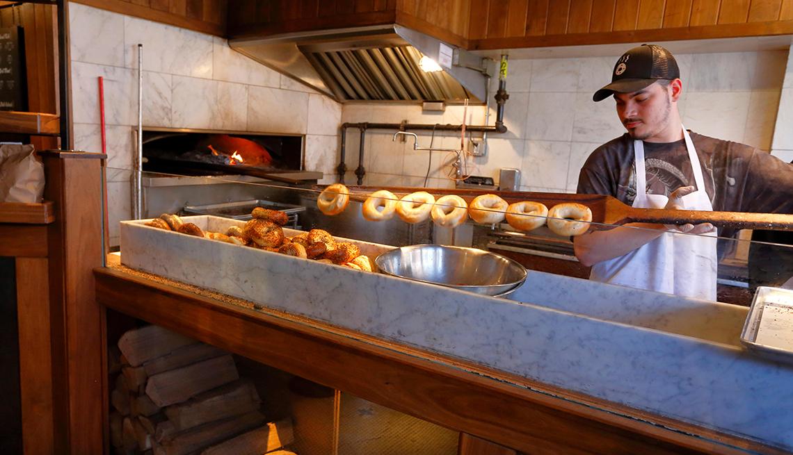 man making bagels in kitchen of bagel shop