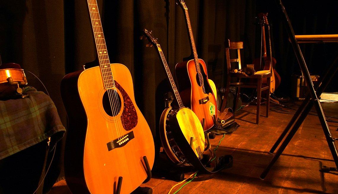 Instrumentos musicales de cuerda puestos sobre el piso de un escenario.