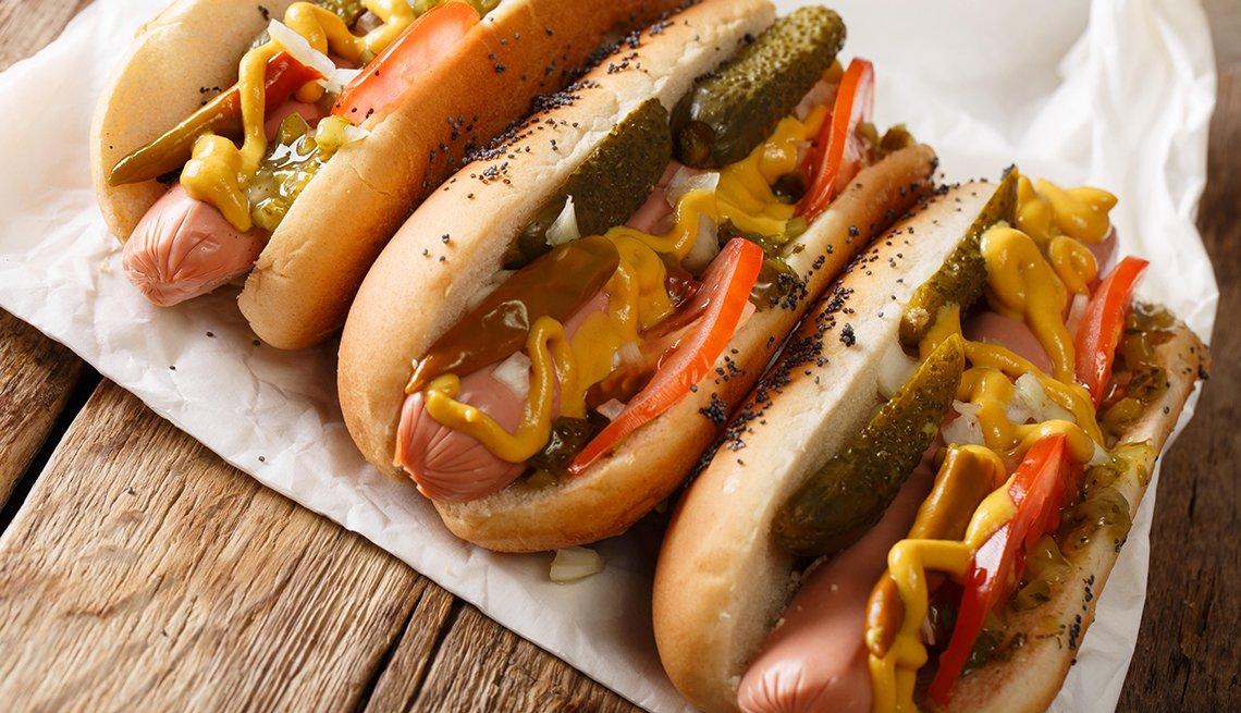 Perritos calientes hechos en casa al estilo de Chicago con mostaza, tomates, pepinos conservados en vinagre y cebollas.