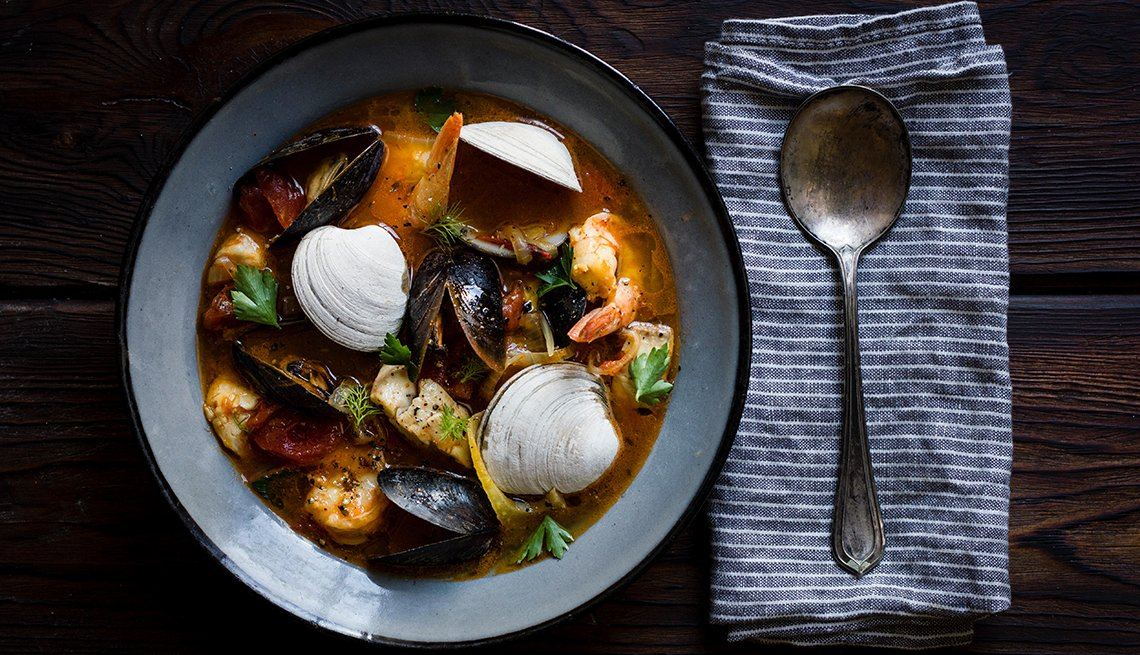 a bowl of cioppino with a spoon on a napkin
