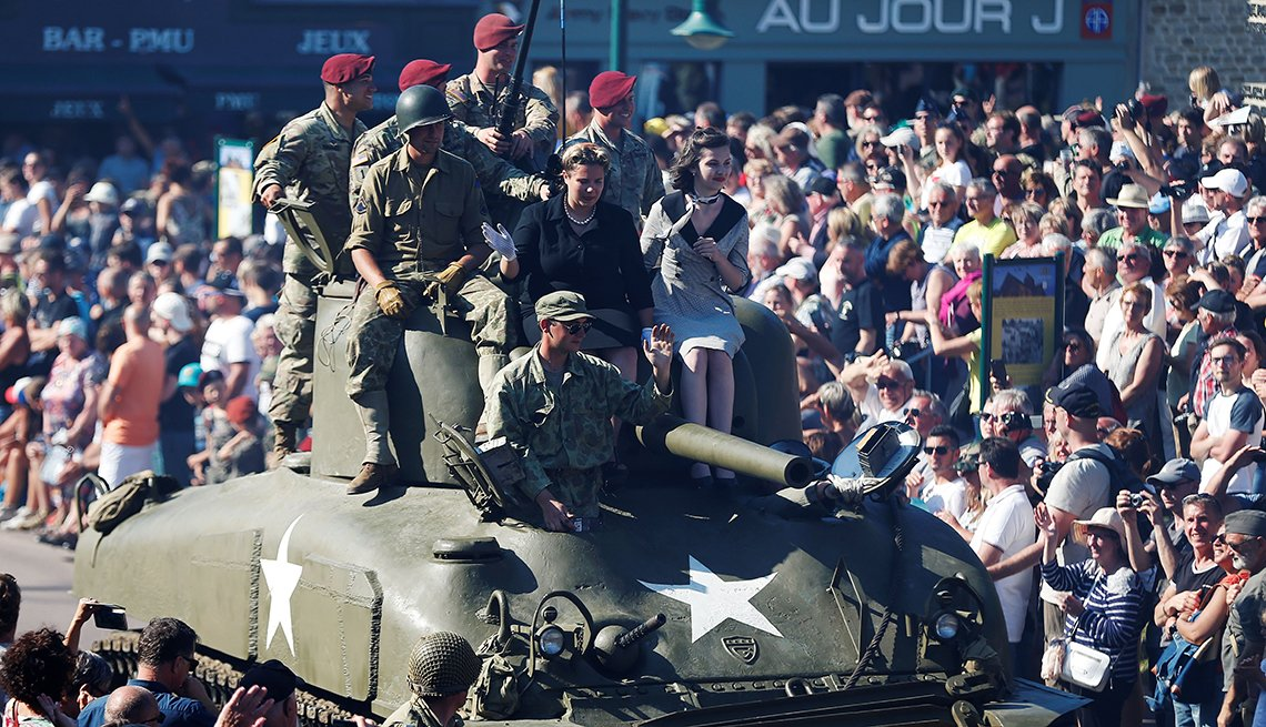 Entusiastas de la Segunda Guerra Mundial están sentados en un tanque de guerra durante un desfile en Sainte-Mere-Eglise, en el noroeste de Francia, el 3 de junio de 2018.