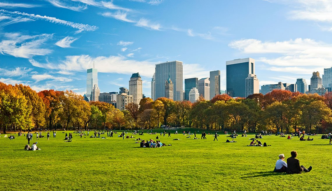People relaxing in Central Park, New York City, in Autumn, looking towards the Central Park South skyline from Sheep Meadow.