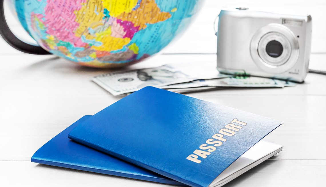 Passports with world map globe, photo camera and money on the table.