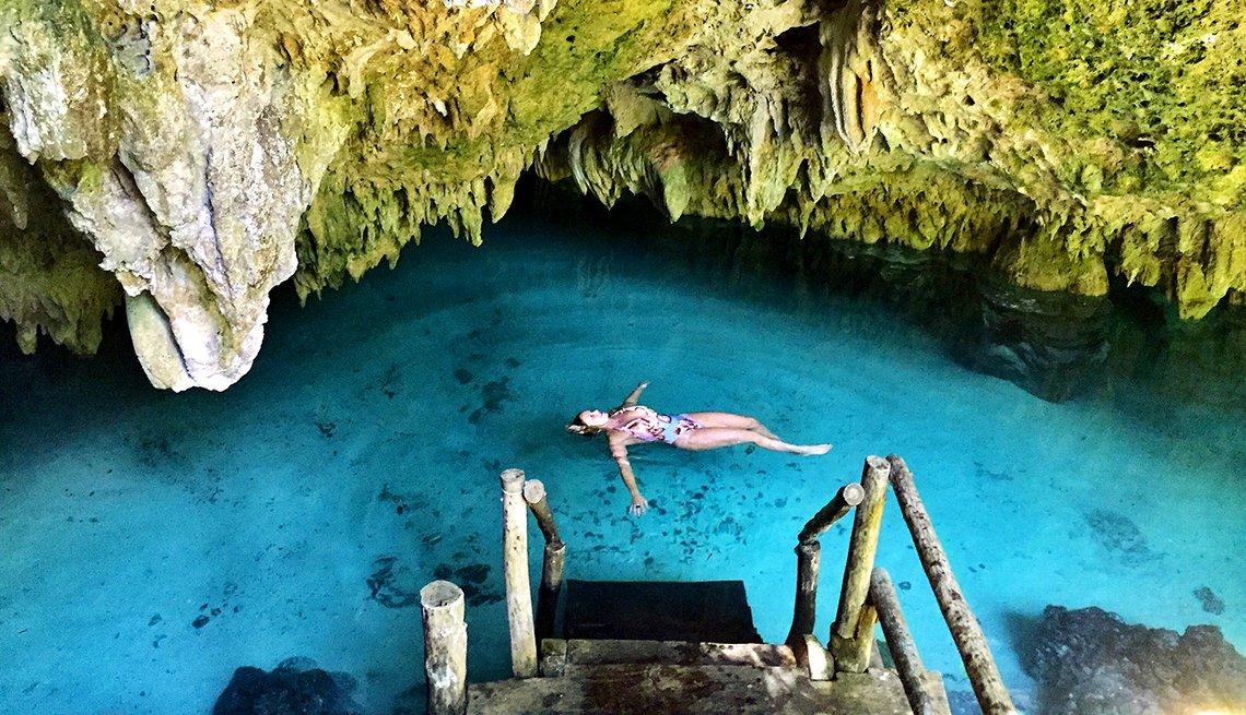 Mujer nada en un lago entre rocas