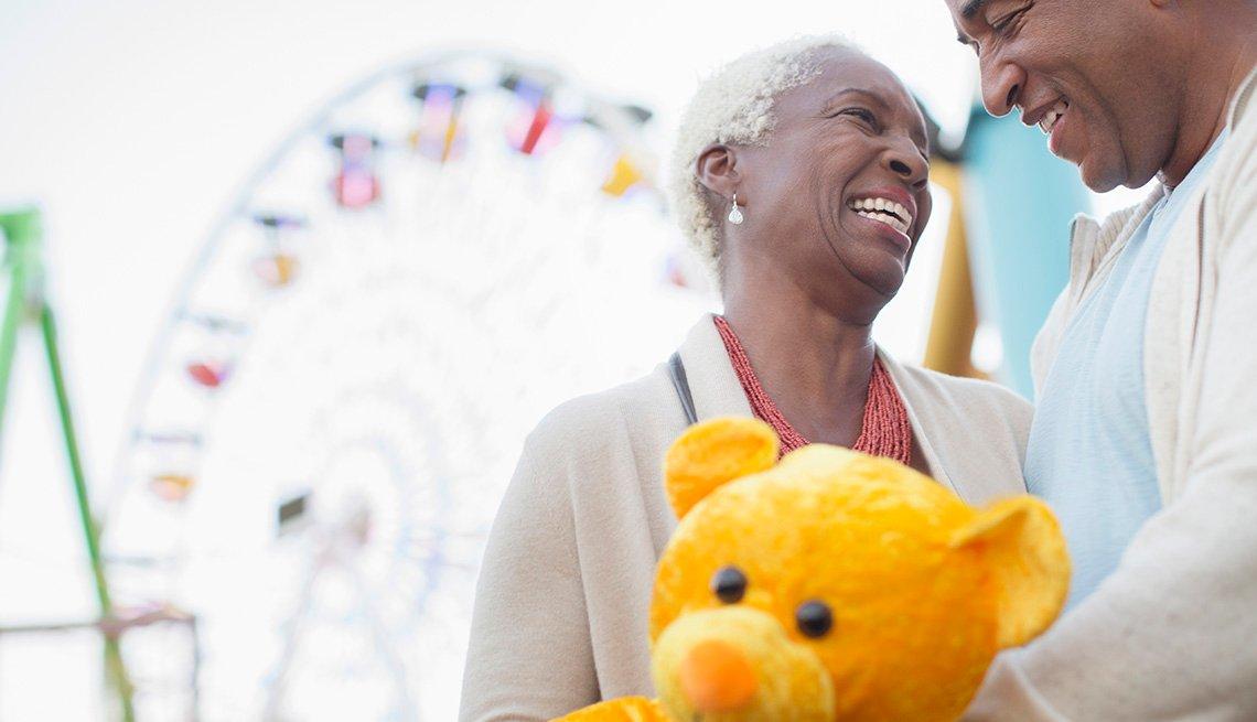Pareja mayor sonriendo en un parque de atracciones