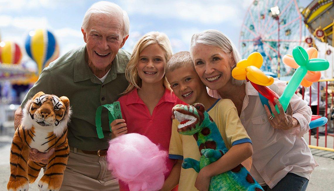 grandparents with grandkids smiling at an amusement park