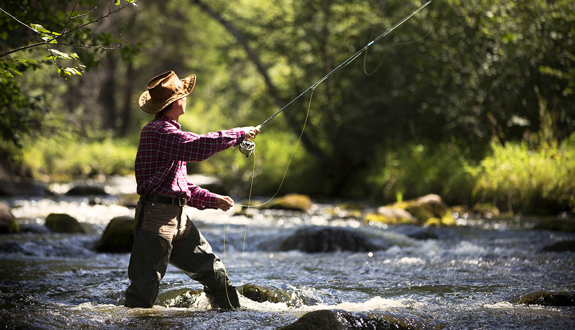 Fly fisherman stands knee deep in river casting his line