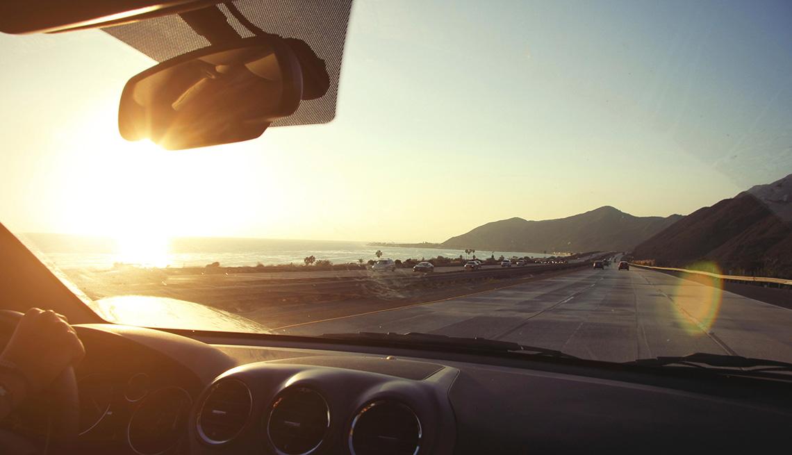 Mujer conduce su auto en una carretera de la costa pacífica de Estados Unidos