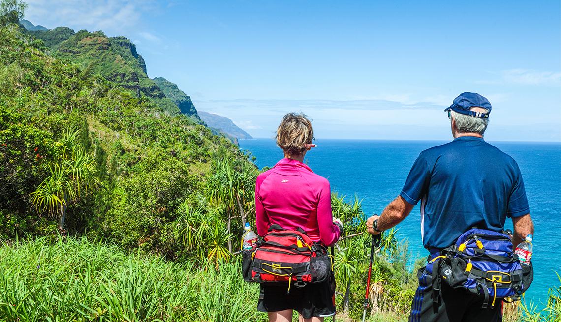 Dos excursionistas disfrutan de la vista de la costa de Na Pali en Kauai