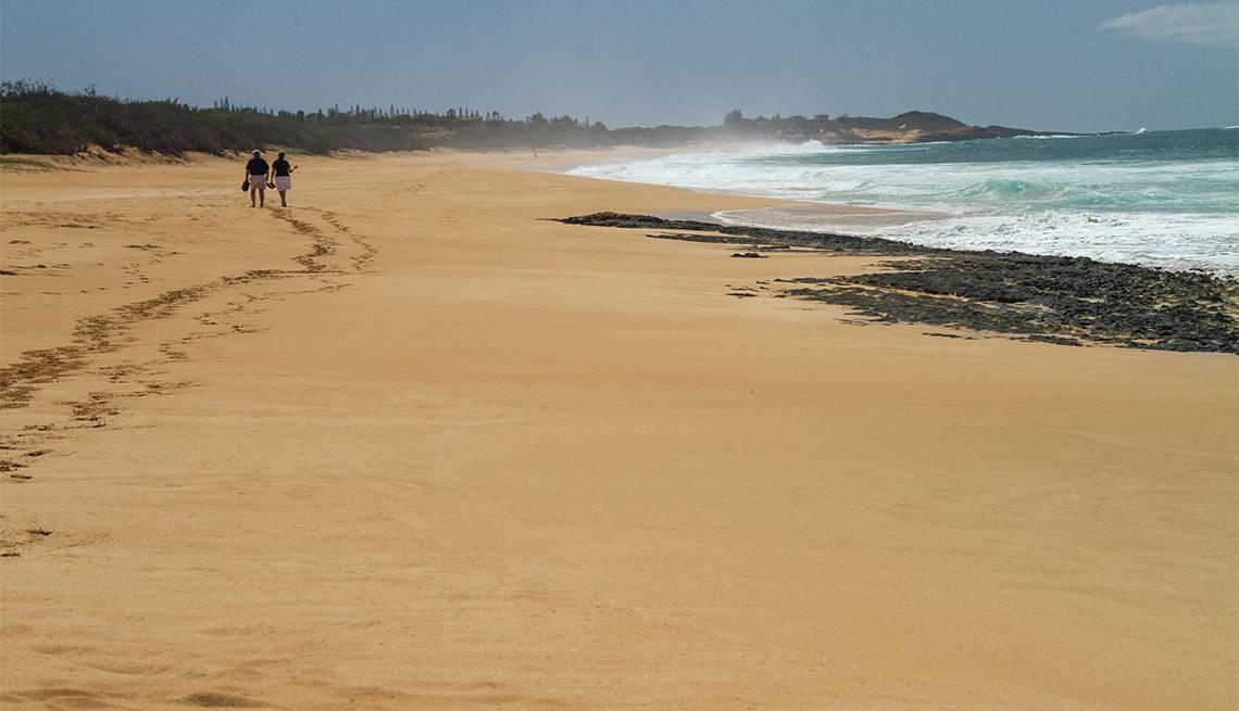 Pareja da un paseo romántico por una playa desierta tropical en Molokai, Hawái