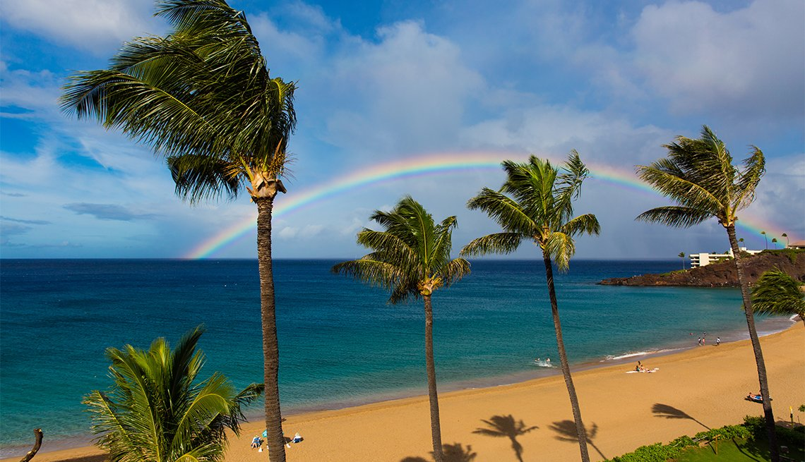 A perfect rainbow on Kaanapali Beach, Maui, Hawaii, forming over Black Rock and into the beautiful sea.