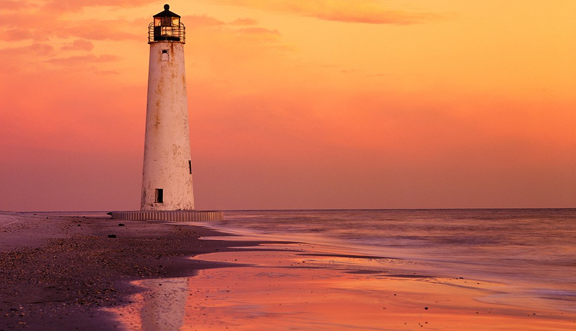 The sun is setting with a lighthouse in Saint George Florida