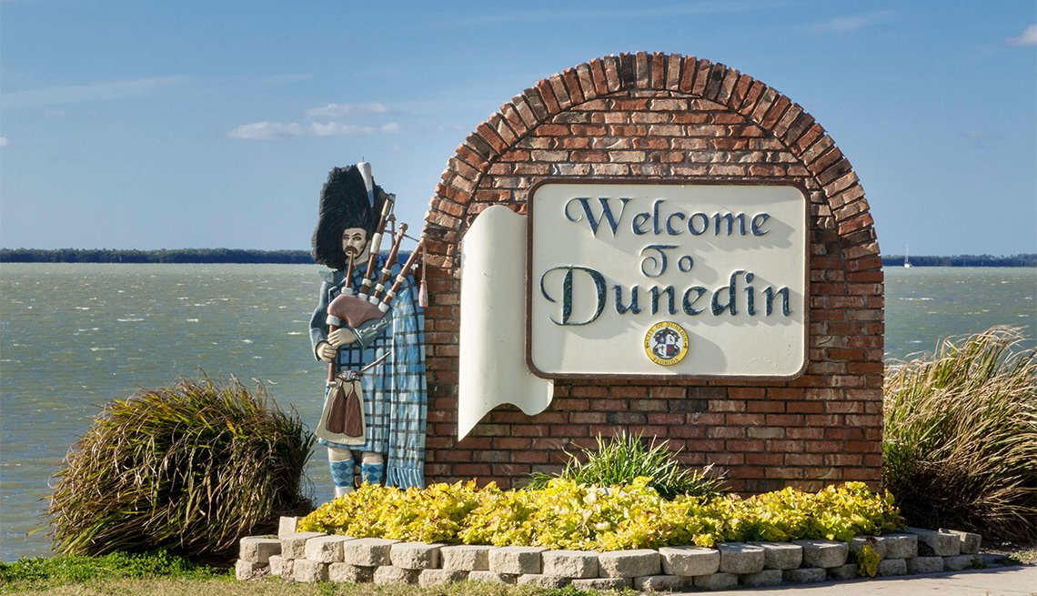 statue of man with bag pipes standing next to the Welcome to Dunedin sign