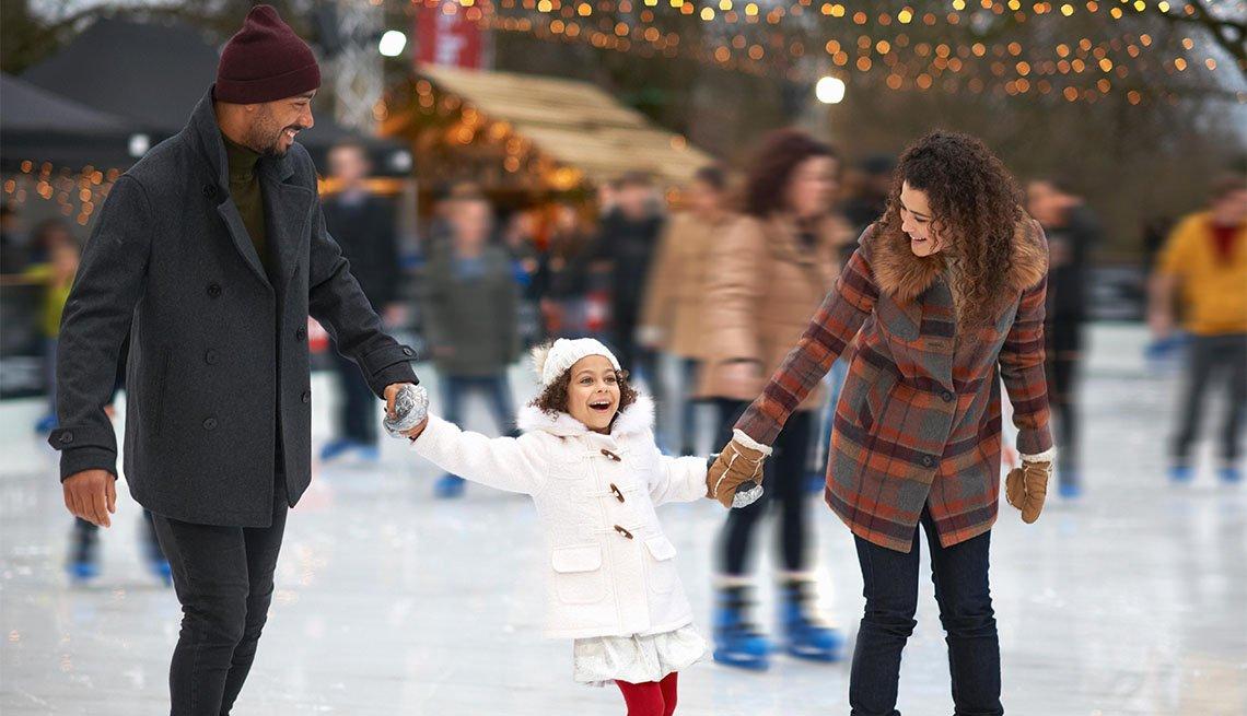 item 3 of Gallery image - Niña va cogida de la mano de sus padres mientras patina sobre hielo