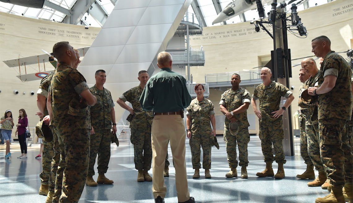 Docent surrounded by Marines at the National Museum of Marine Corps