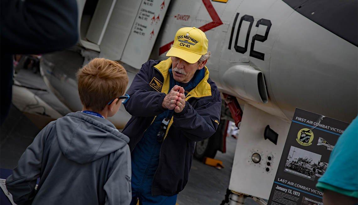 Voluntario habla con un visitante del USS Midway