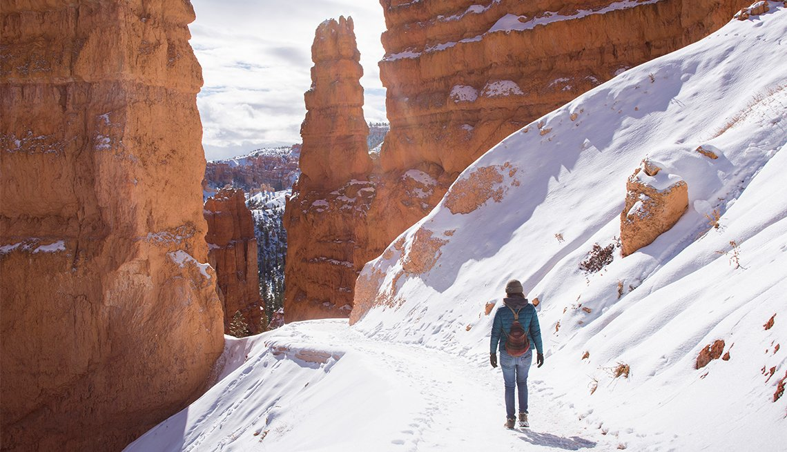 female hiker walking on a trail in Bryce Canyon National Park during winter