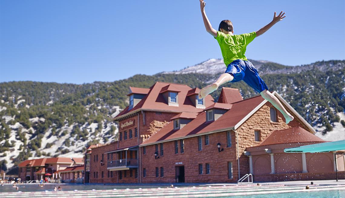Niño saltando a la piscina en Glenwood Hot Springs