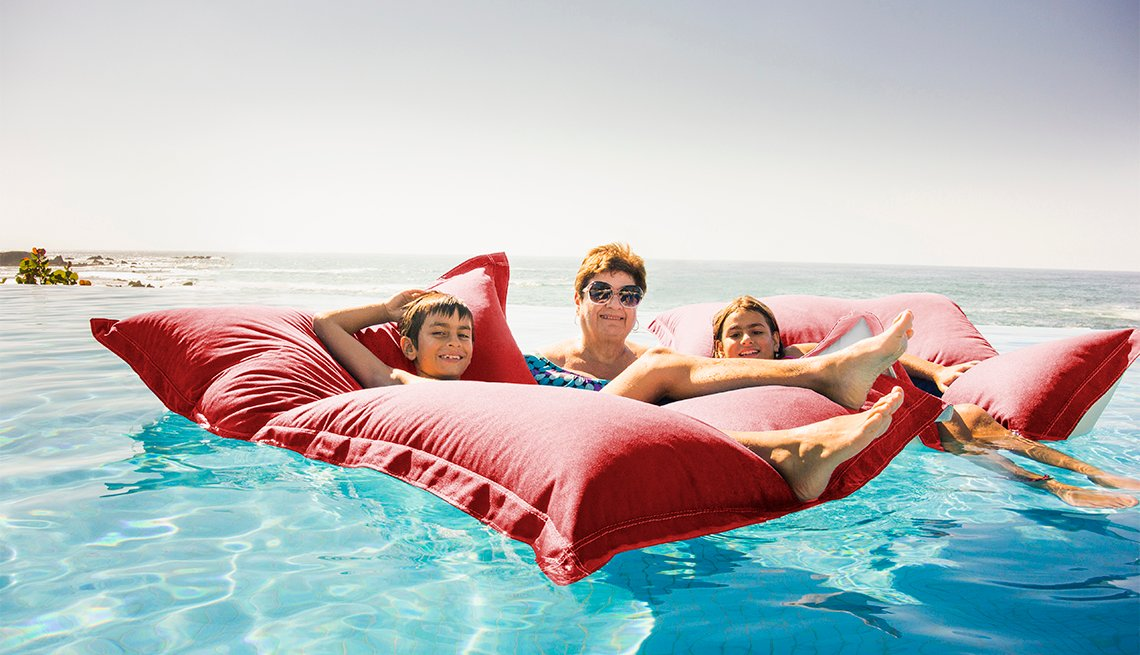 Grandmother and grandchildren relaxing on pool raft