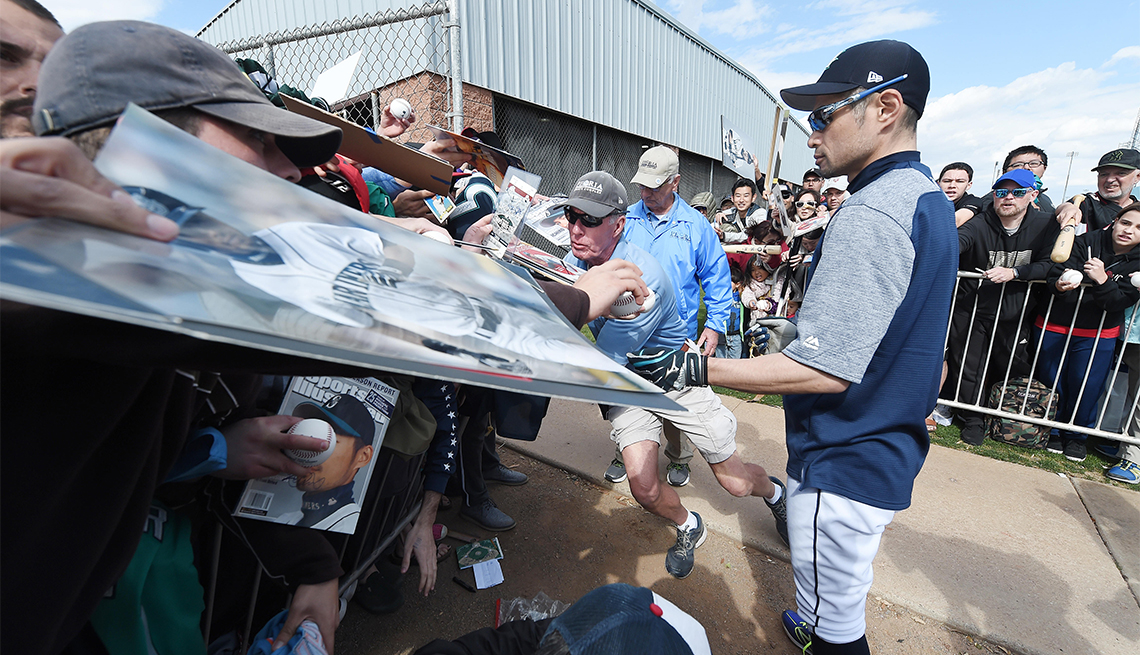 Ichiro Suzuki of the Seattle Mariners signs autographs for fans during a spring training camp at Peoria Sports Complex