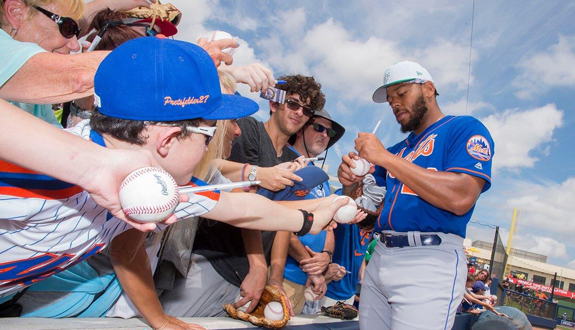 A New York Mets player signs autographs for fans at spring training