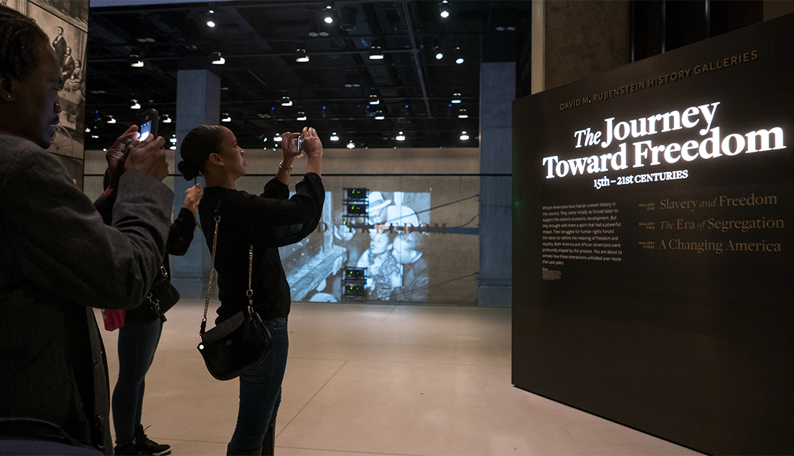 item 11 of Gallery image - Guests tour the Slavery and Freedom exhibit at the Smithsonian's National Museum of African American History and Culture (NMAAHC)