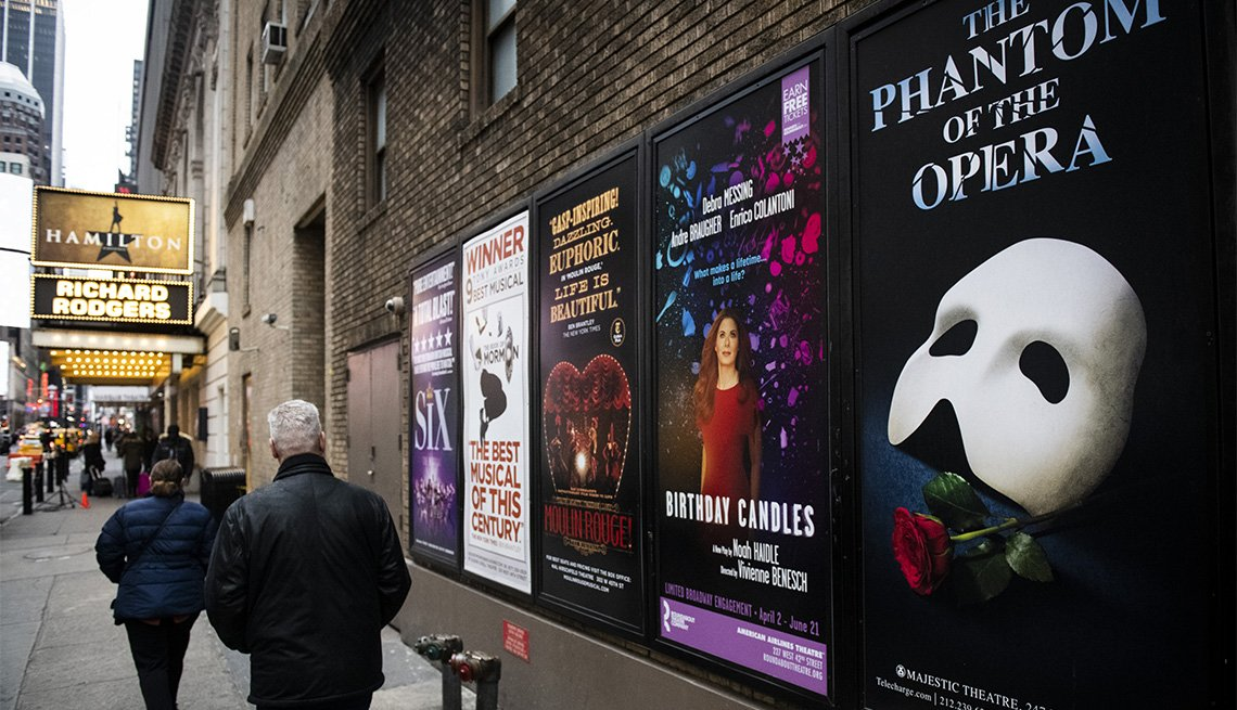 Pedestrians walk past Broadway posters in the Times Square neighborhood of New York among the coronavirus pandemic