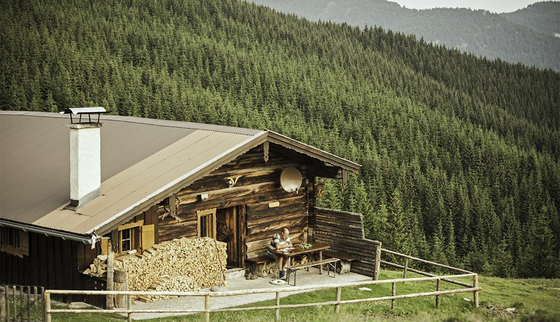 Hombre sentado frente a una cabaña en las montañas