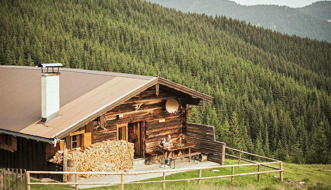 man sitting on log cabin porch
