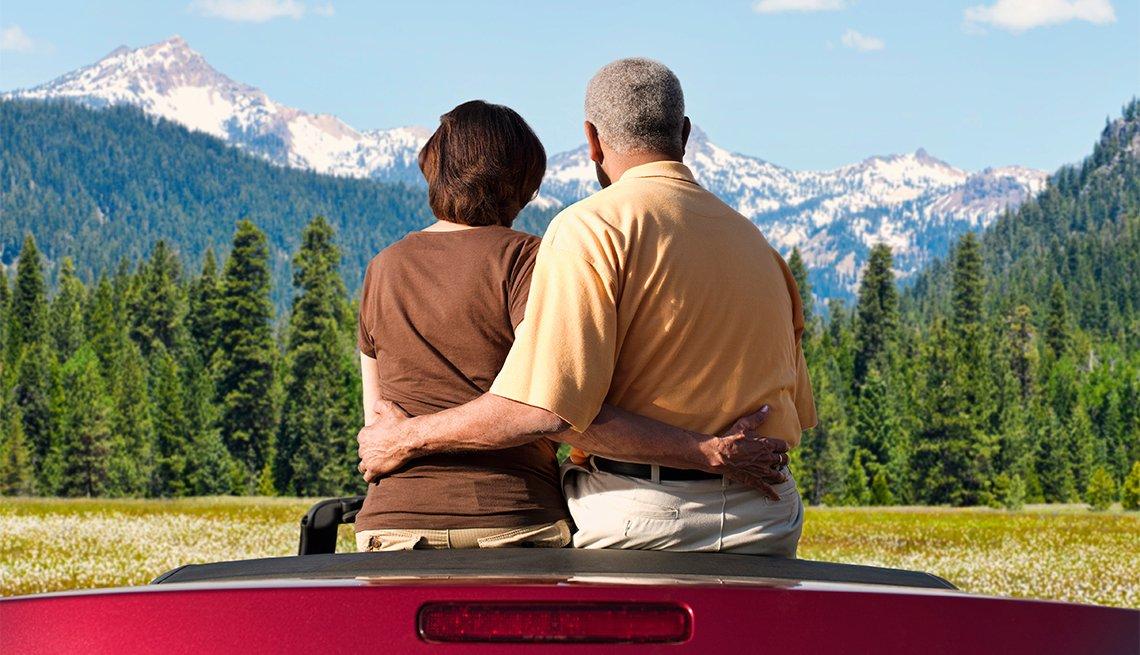 Pareja sentada en un auto convertible mientras observan árboles y montañas
