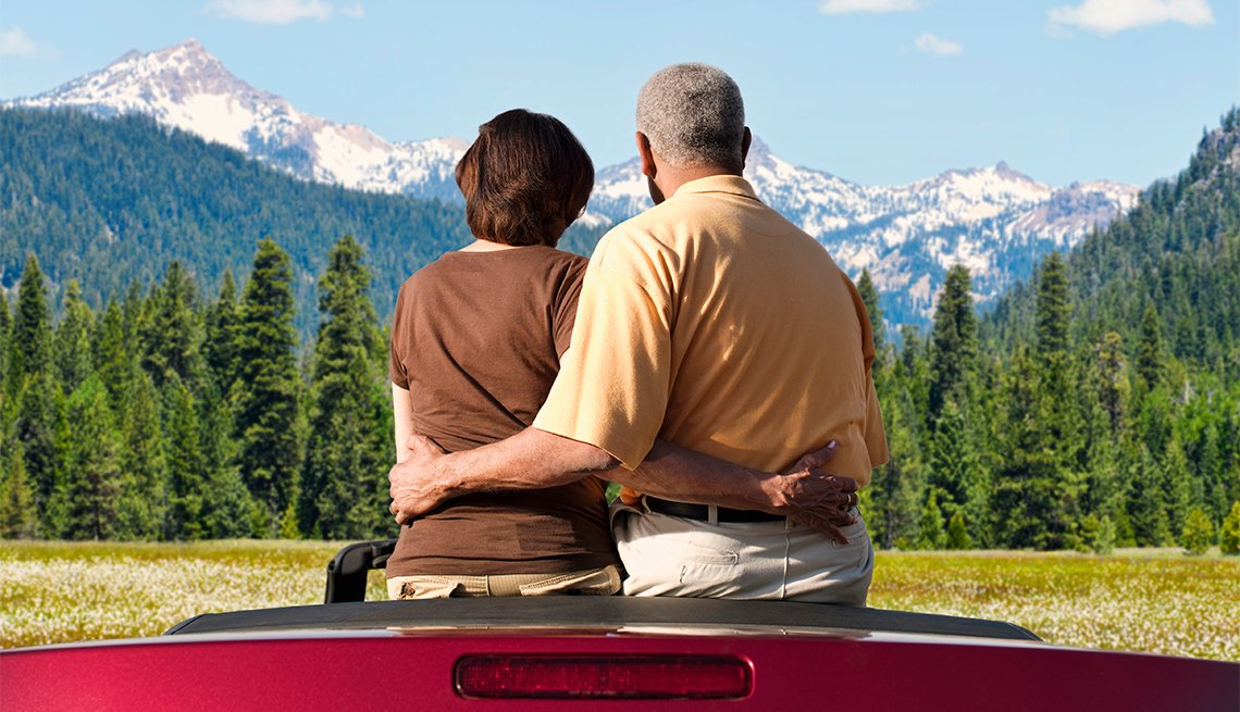 couple sitting in convertible admiring mountain scenary
