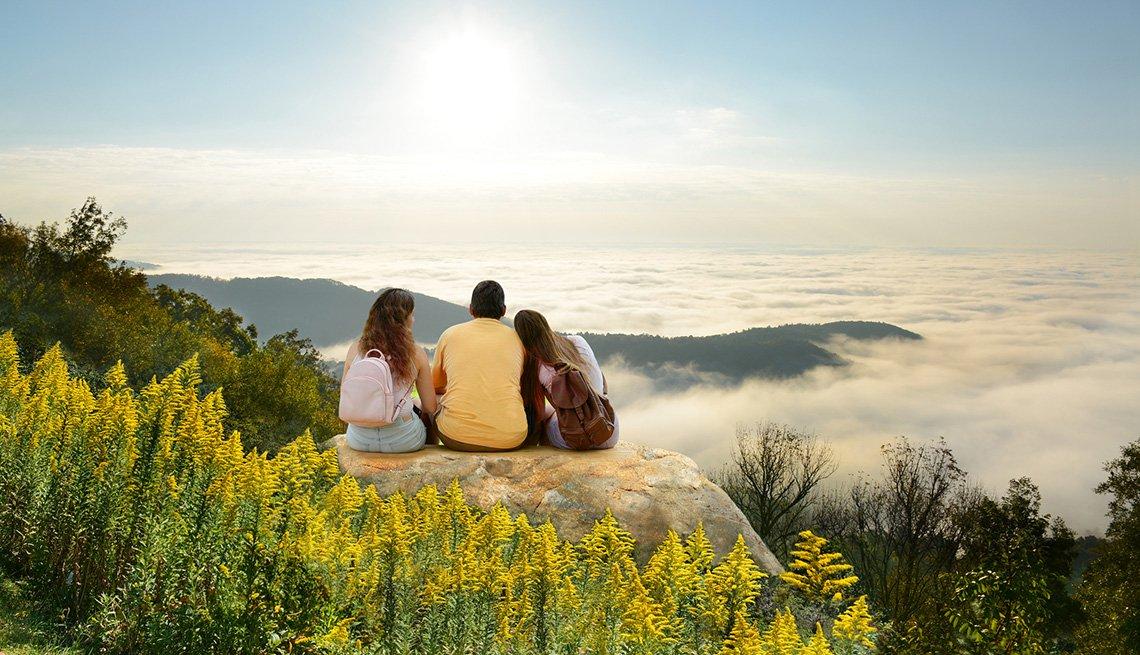Un hombre junto a su esposa e hija sentado en la cima de una montaña