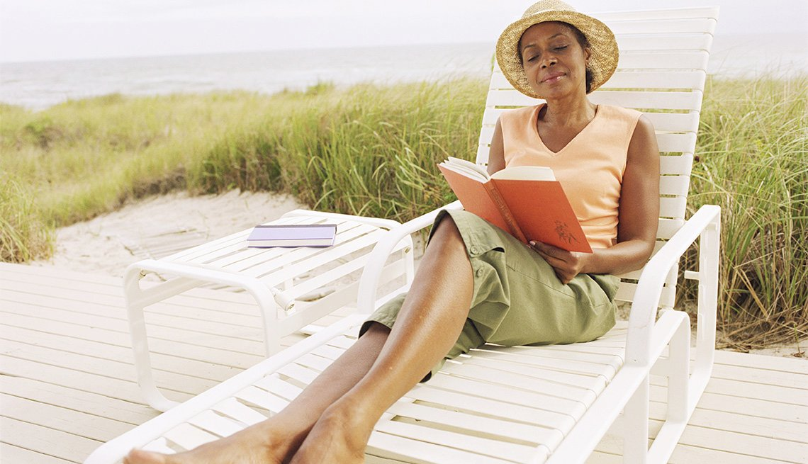 woman reading a book on a lounge chair at the beach