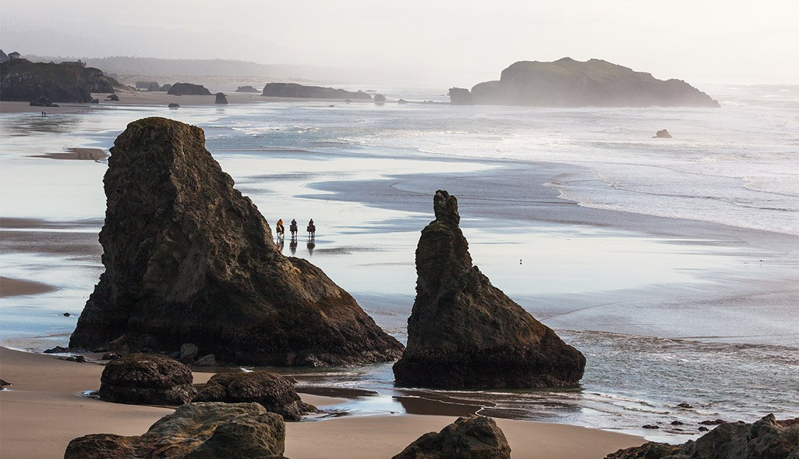 three people touring the beautiful beach in Bandon Oregon on horses