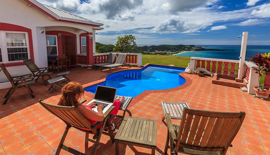 Woman with laptop at poolside overlooking Grande Anse Bay. Grenada W.I.