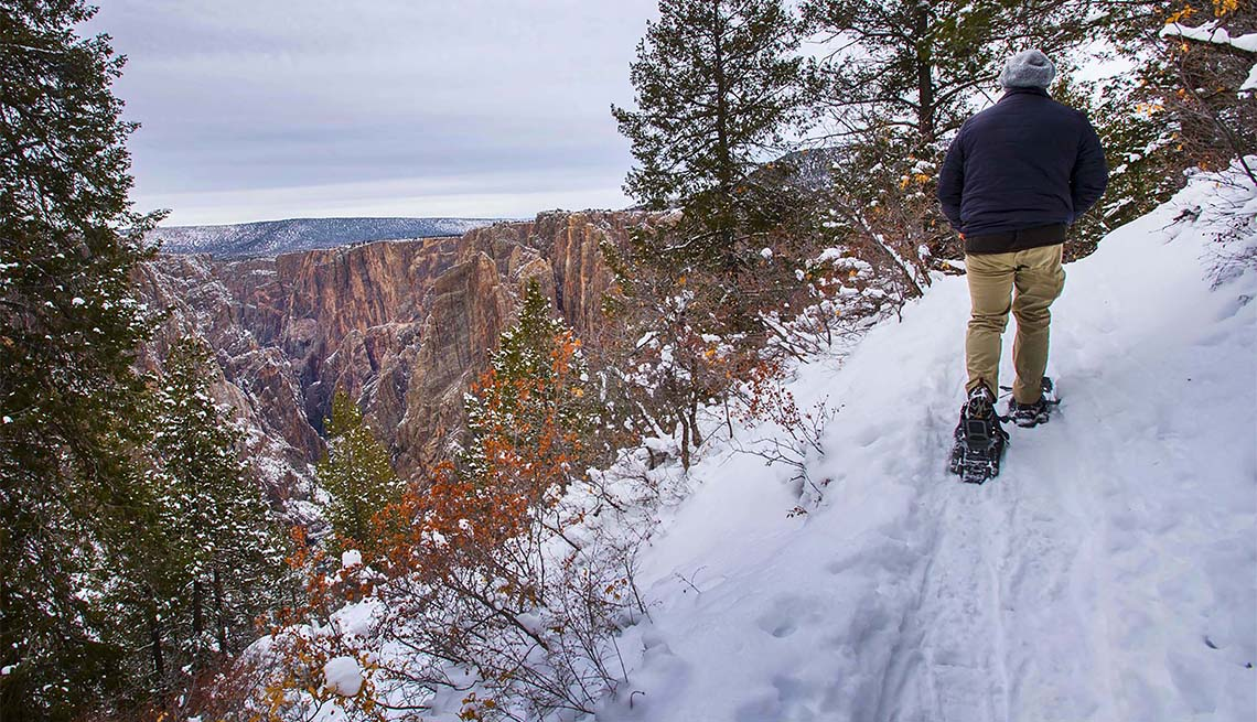 item 1 of Gallery image - Seth Boster snowshoes the 2-mile Oak Flat Loop Trail on the south rim of Black Canyon
