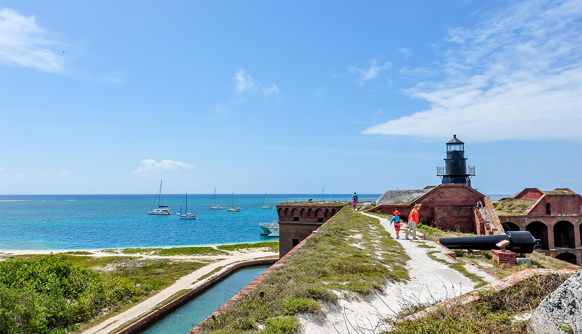 item 8 of Gallery image - Kids explore Fort Jefferson at Dry Tortugas National Park with their father, walking along the roof with view of lighthouse, water and sailboats