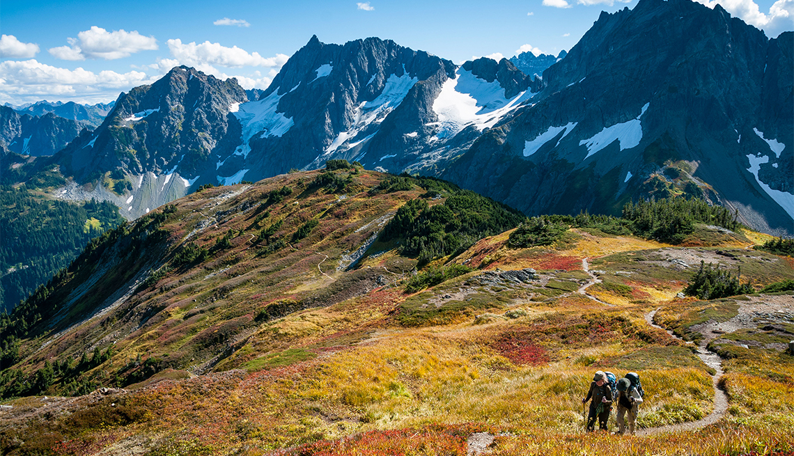 item 7 of Gallery image - Couple with backpacks hiking on Sahale Arm Trail, Cascade Pass, North Cascades National Park