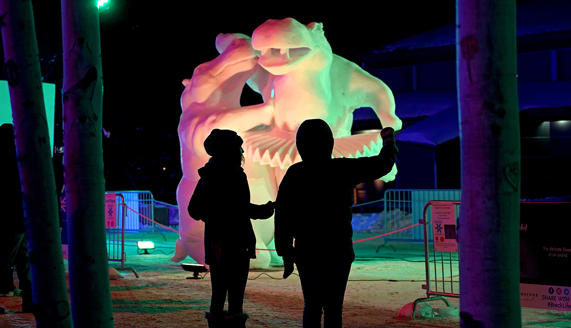 Dos personas obervan una escultura de hielo.