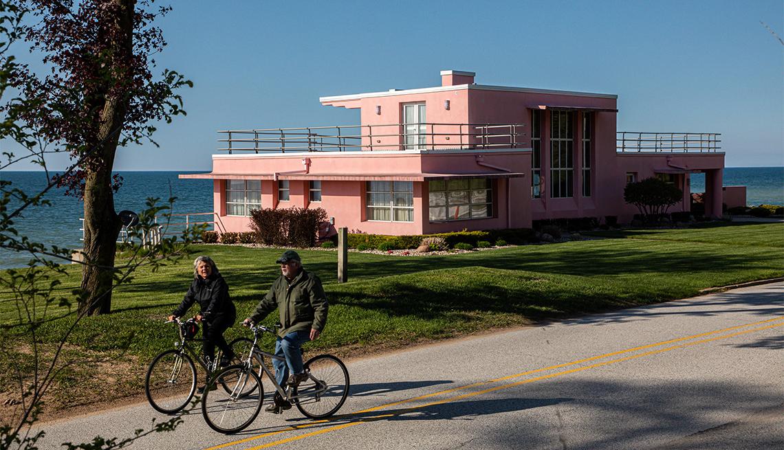 Ciclistas pasan junto a una casa frente al mar