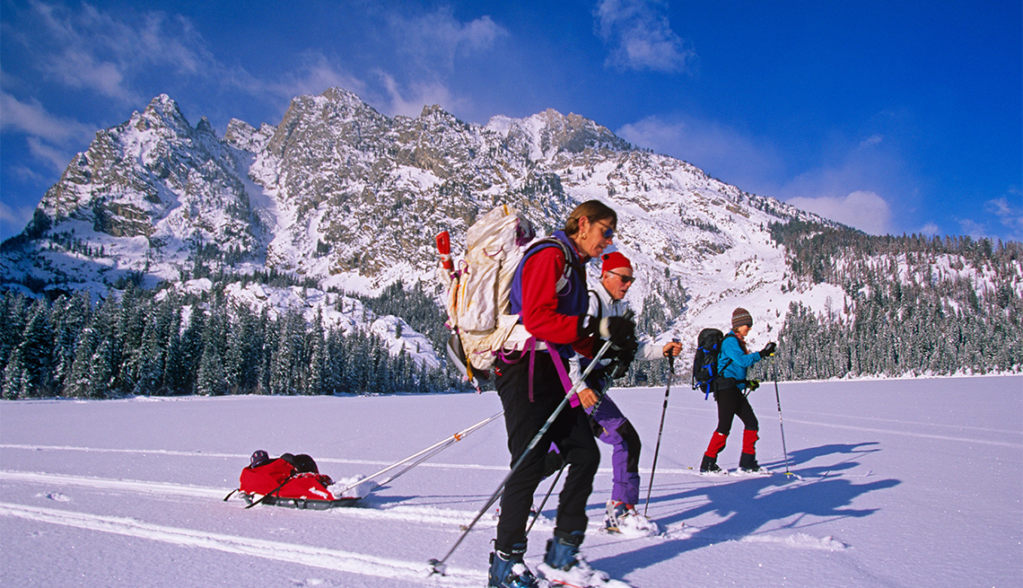 item 3 of Gallery image - Cross Country skiing across a frozen lake in the Grand Tetons National Park.