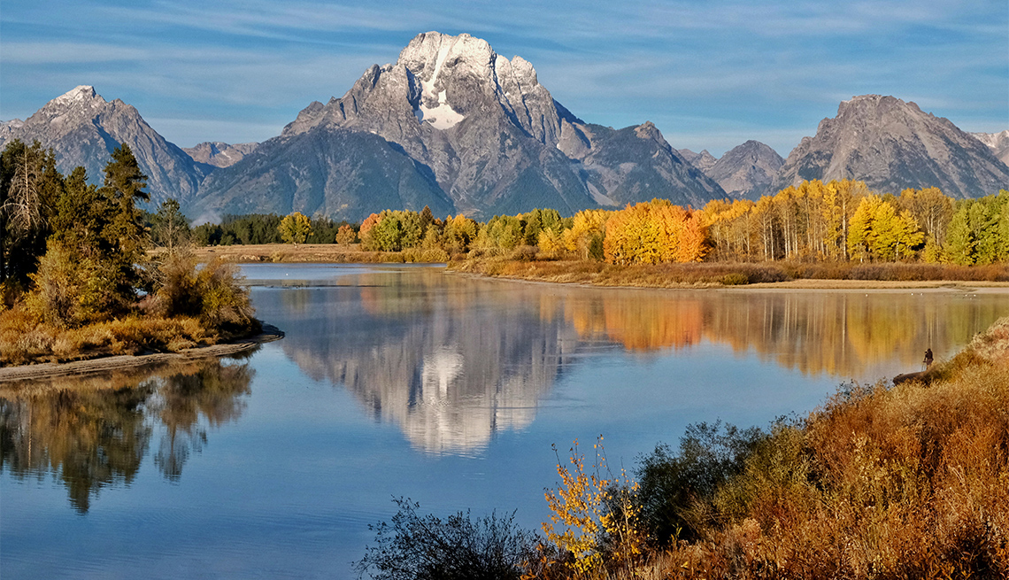 item 4 of Gallery image - A solitary figure in the distance photographs the autumn foliage at Grand Teton National Park in Wyoming